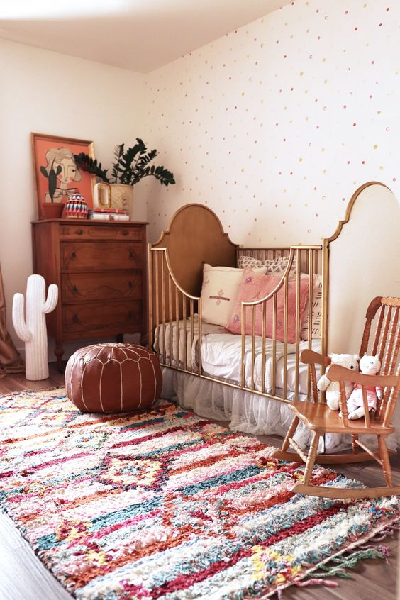 a beautiful boho nursery with a polka dot wall, a bright boho rug, wooden and rattan furniture, a leather ottoman, greenery and a cactus