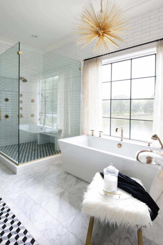 a beautiful transitional space with a catchy tub, a sunburst chandelier, a faux fur stool and mosaic tiles