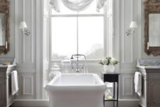 a beautiful vintage-inspired bathroom with a white tub, curtain, mirrors and chic vanities plus a rug