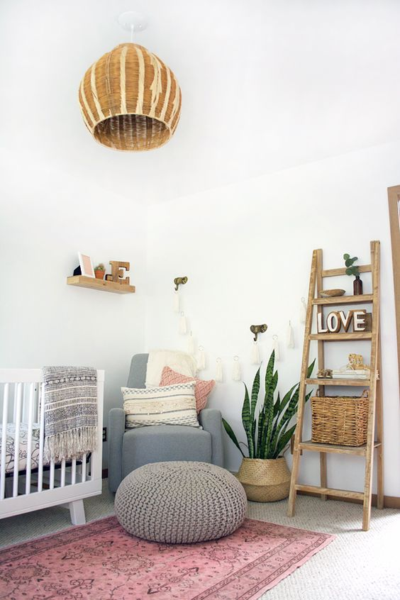 a boho chic nursery with a pink rug, touches of grey, a wicker lamp, a ladder with baskets
