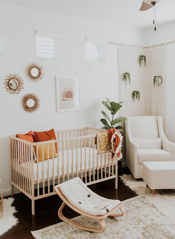 a boho chic nursery with potted greenery, a wooden crib and little rocker, a gallery wall and some boho rugs