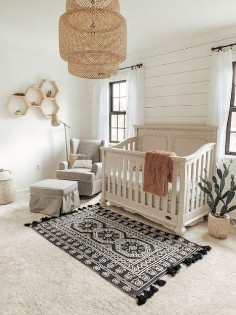 a boho meets vintage nursery with a wicker lampshade, hex shelves, a boho rug, grey furniture