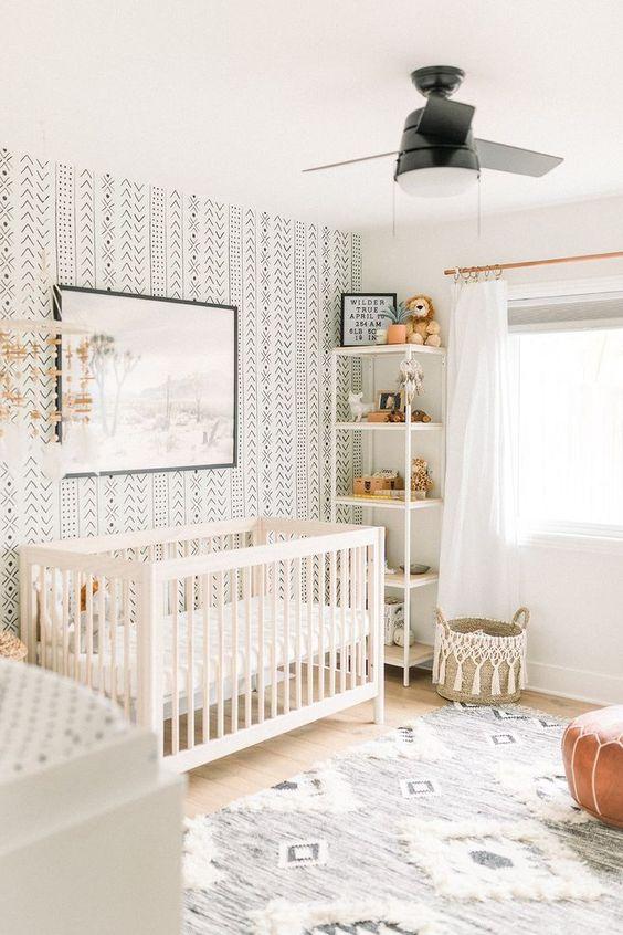 a boho nursery with a folksy print wallpaper wlal, a leather ottoman, a tassel basket and a neutral boho rug