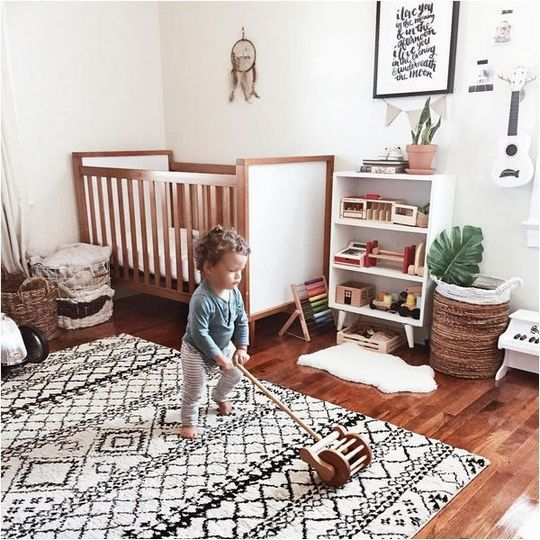 a boho nursery with a pritned rug, baskets, a dream catcher on the wall and some simple stuff
