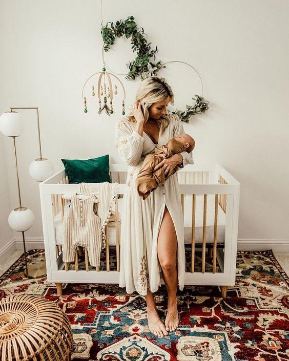 a boho nursery with a white crib, a bright boho rug, a rattan ottoman and some faux greenery wreaths