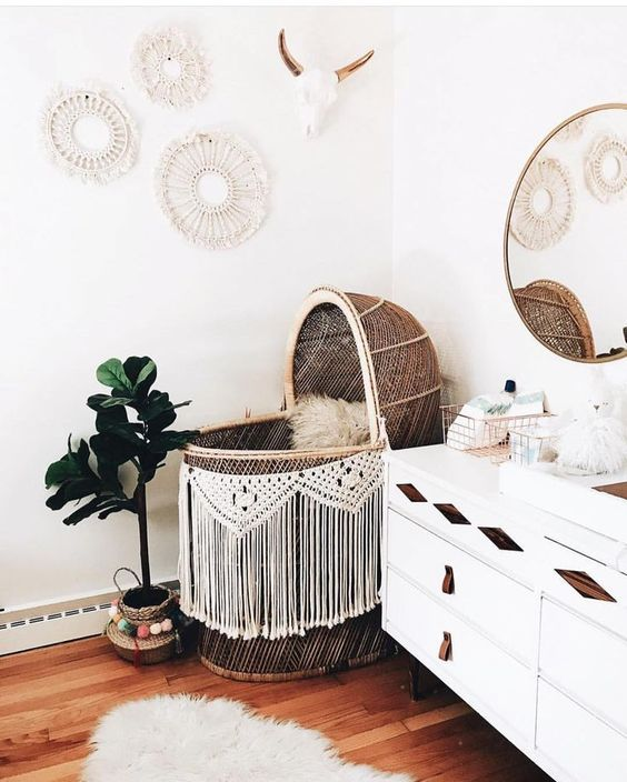 a boho nursery with a wicker bassinet with macrame, a white sideboard with leather touches and a gallery wall of macrame