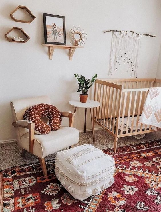 a bright boho nursery with a red boho rug, a white Moroccan pouf, macrame, mid-century shelves and a chic chair