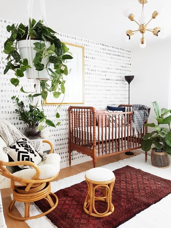 a bright modern boho nursery with a vintage crib, rattan chairs, boho rugs, potted greenery and an elegant chandelier