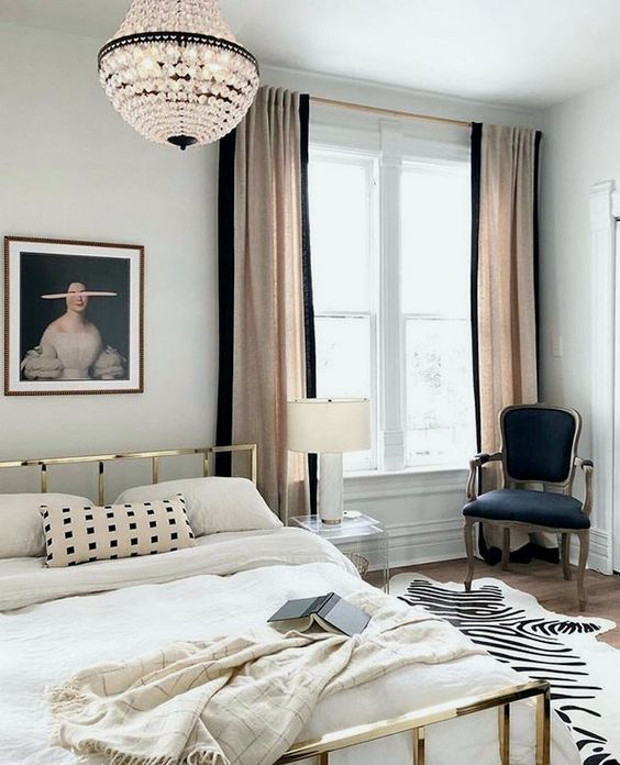 a chic Parisian bedroom with a gold bed, a crystal chandelier, a refined chair and blush and black curtains