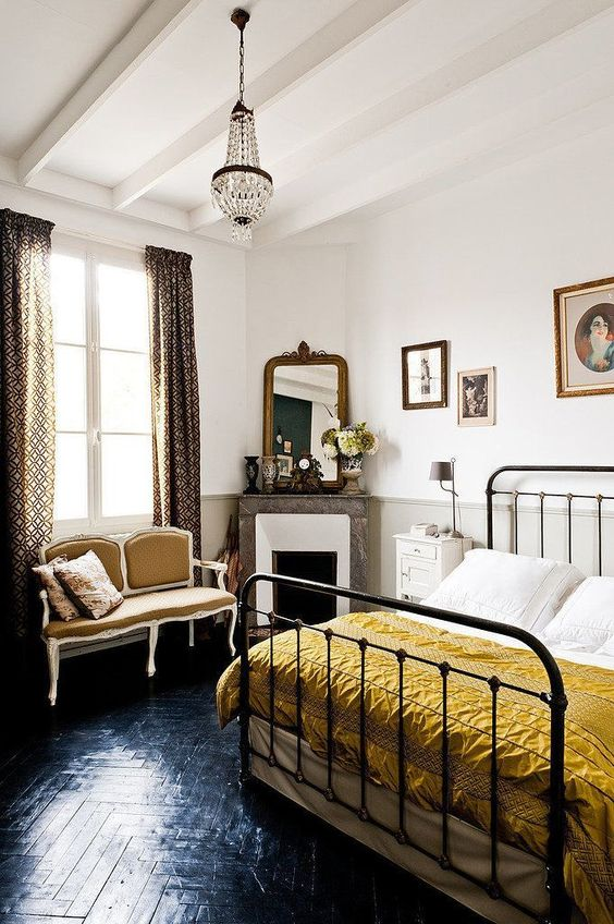 a chic Parisian bedroom with printed curtains, a crystal chandelier, a retro metal bed, a chic mustard loveseat and a marble clad fireplace