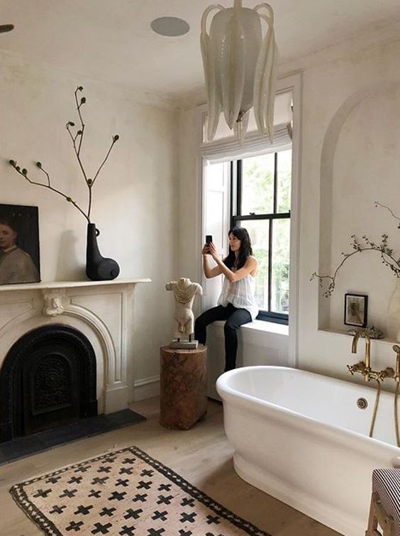 a chic Parisian space in neutrals, with blakc touches, a faux fireplace, a statement chandelier and a sculpture