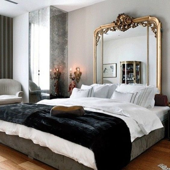 a chic Parisian space with a statement mirror headboard, a large bed, mirror panels and an antique lamp