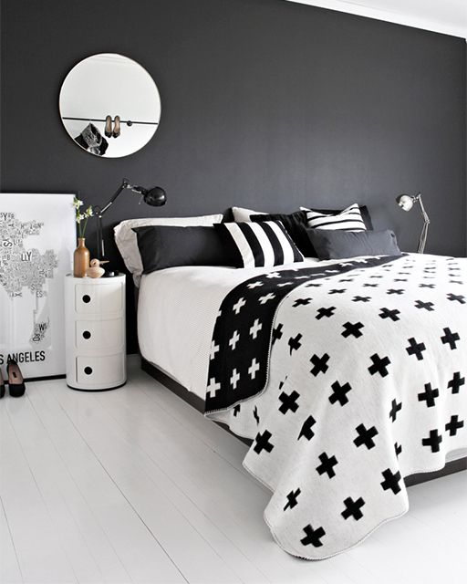 a chic Scandinavian bedroom with a black accent wall, printed bedding, a round tube nightstand and stylish lamps