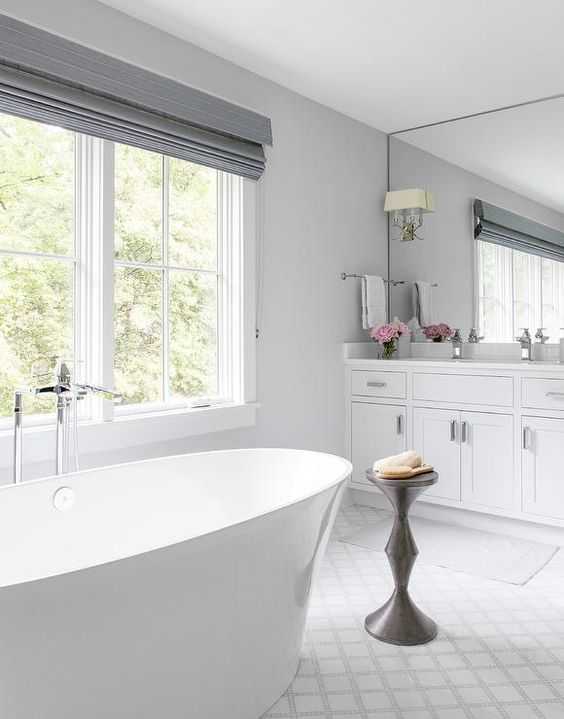 a chic and elegant bathroom with grey shades, a chic stand, a contemporary tub and a large mirror