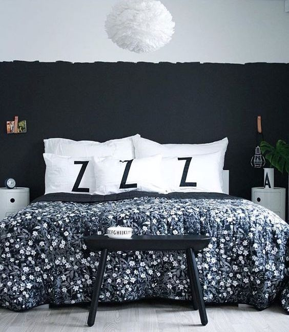a chic bedroom with a black accent wall, a black stool, rounded nightstands and a fluffy lamp