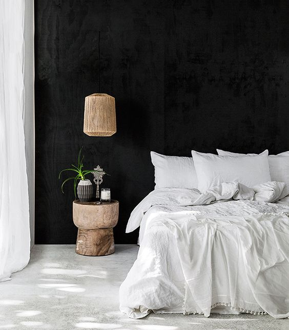 a chic black and white bedroom with black walls, a white floor, white textiles and a wooden lamp and nightstand