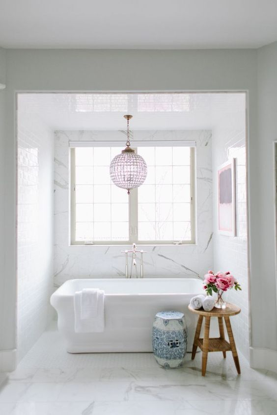 a chic transitional space with a lavender chandelier and artwork, an amazing blue porcelain stool and a chic tub