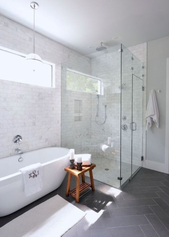 a chic transitional space with marble and grey tiles, a contemporary oval tub, a wooden stool and a seamless shower