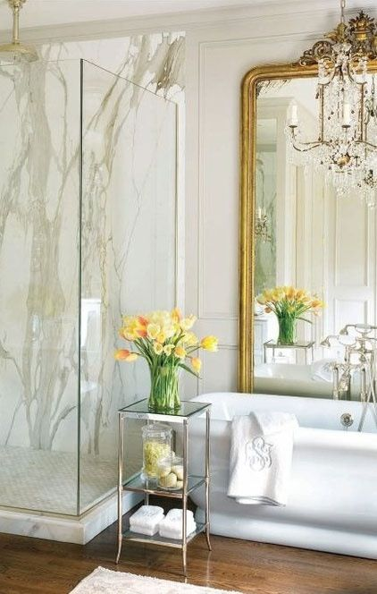 a chic vintage bathroom with white stone tiles, paneling, a sstatement mirror and a crystal chandelier