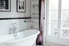 a chic vintage-inspired bathroom with a clawfoot bathtub, purple curtains, a crystal chandelier, artworks and black and white tiles