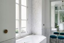 a contemporary Parisian bathroom done with white marble, chevron clad floor, teal stools and cabinets on the walls