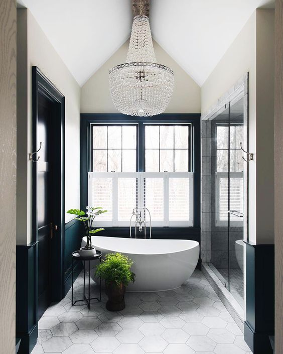 a contemporary Parisian bathroom with an oval tub, a large crystal chandelier, black and white walls and a hex tile floor