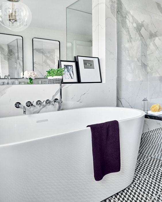 a contemporary Parisian bathroom with an oval tub, artworks, white marble tiles and a geometric floor