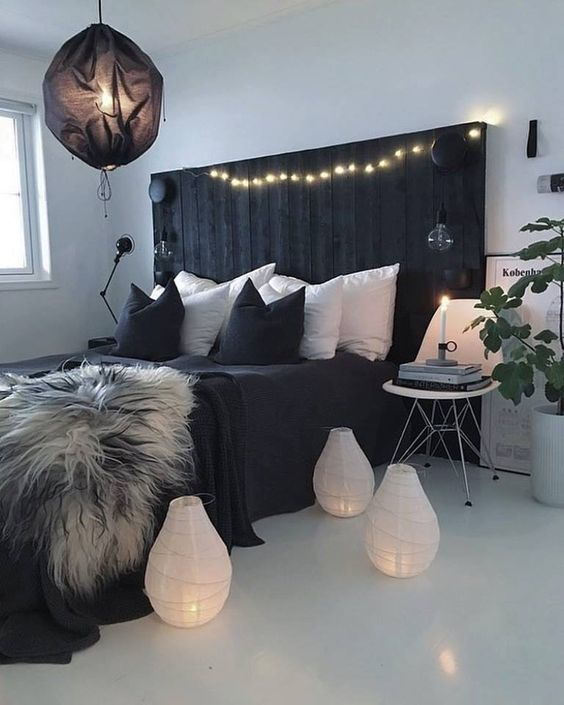 a contemporary boho bedroom with a black rustic bed, mismatching nightstands, a black lamp and white candle lanterns