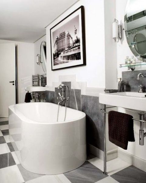 a contemporary monochromatic bathroom with a statement artwork, an oval tub, a free standing sink and a checked floor