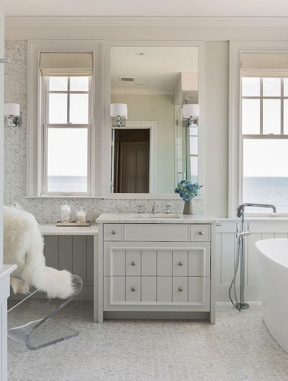 a contemporary tub, windows with sea views and a vintage meets contemporary vanity plus an acrylic chair