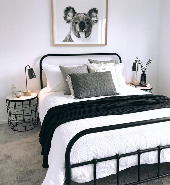 a cozy small bedroom in black and white, with a black metal bed, monochromatic bedding and a stylish industrial nightstand