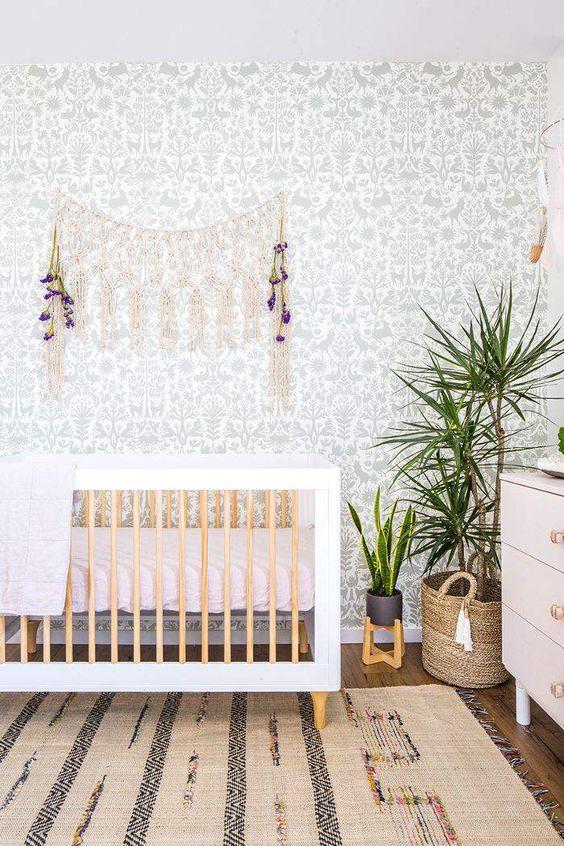a cute boho nursery with a botanical wallpaper wall, a boho rug, a crib, macrame and potted greenery
