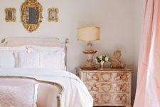 a dreamy Parisian bedroom done in neutrals and blush, with an arrangement of mirrors, refined vintage furniture with gold inlays