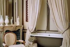 a fantastic neutral vintage-inspired Parisian bathroom with canopies, a bathtub, a vintage chair and a faux fireplace