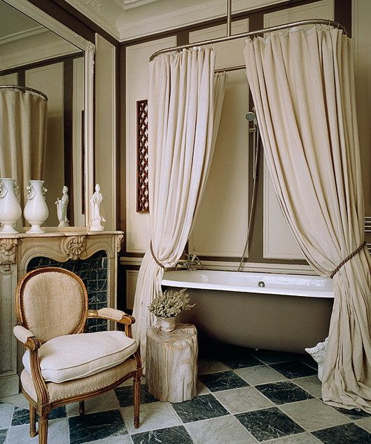 a fantastic neutral vintage inspired Parisian bathroom with canopies, a bathtub, a vintage chair and a faux fireplace