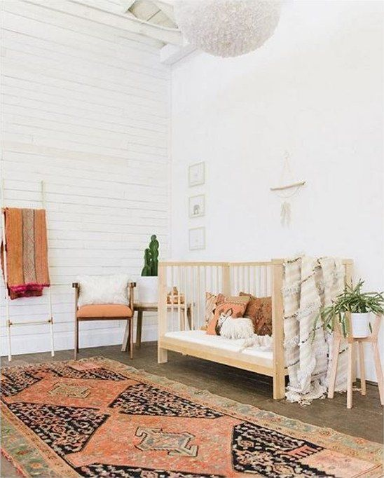 a free-spirited nursery with a boho rug, a wooden crib, potted greenery and touches of faux fur here and there