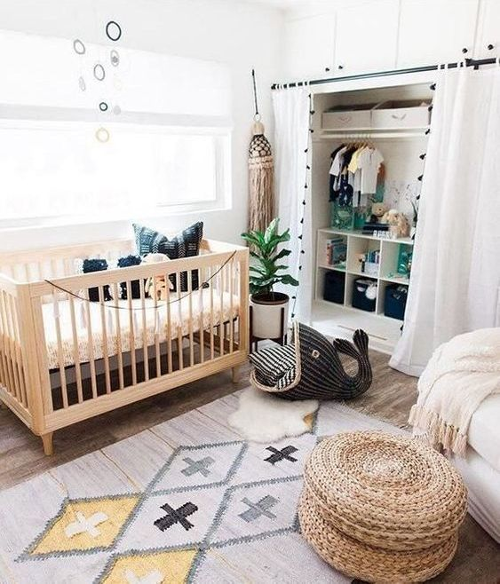 a fun boho nursery with a printed rug, a jute ottoman, a wooden crib, an oversized tassel and a large fun wicker whale for storage