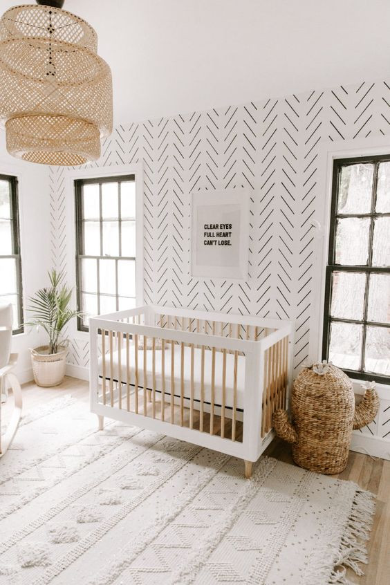 a gender neutral boho nursery with a wicker cactus, a Moroccan blanket rug, a folksy wallpaper wall, a wicker lamp and potted plants