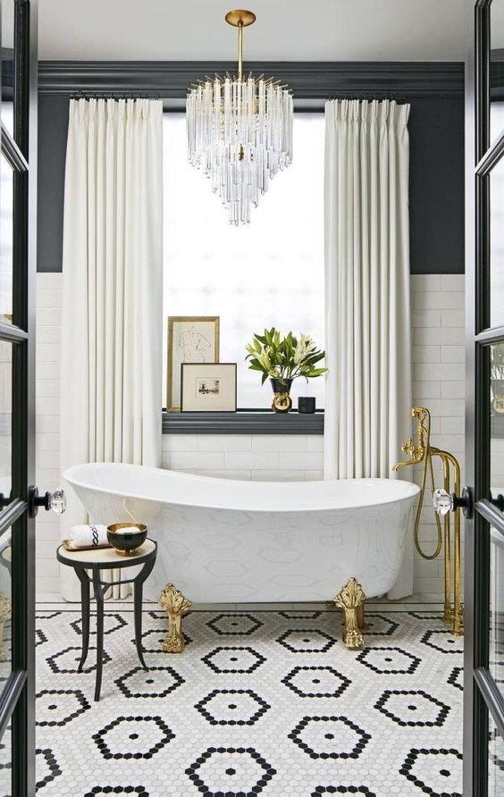 a glam Parisian bathroom with a mosaic tile floor, a clawfoot bathtub, a statement chandelier, gold touches and artworks