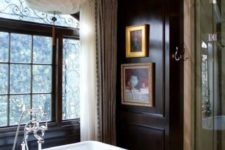 a gorgeous vintage bathroom with black walls, a vintage tub, a gorgeous chandelier and artworks