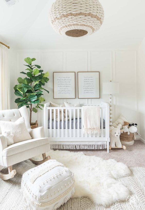 a heavenly creamy nursery with a wicker lamp, a faux fur rug, a rocker, a white crib and a knit rug plus a Moroccan pouf