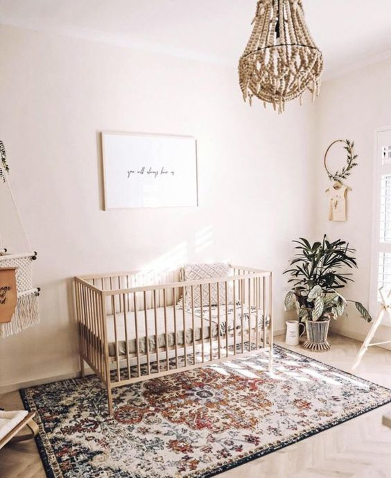 a light-filled boho nursery with a bead chandelier, a boho rug, potted greenery and a minimal artwork