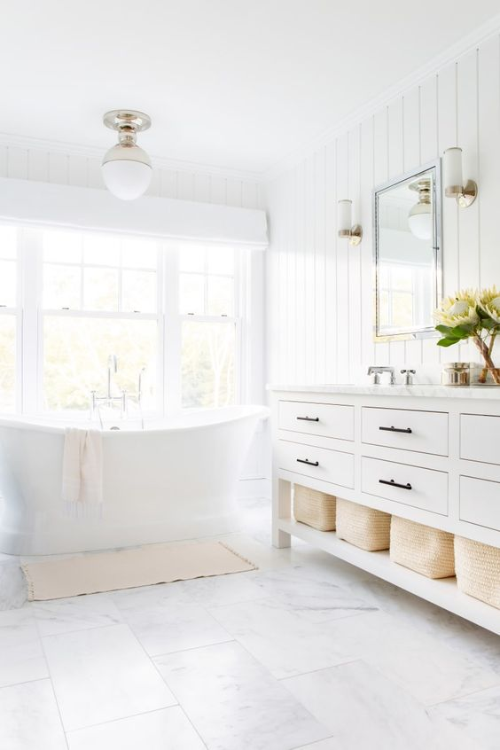 a light-filled transitional white bathroom with a traditional white vanity, a vintage tub and a pendant lamp plus marble tiles