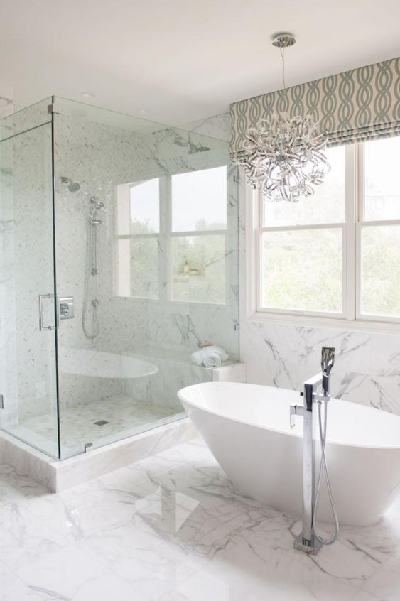 a luxurious transitional space with a fantastic chandelier, an oval tub, marble tiles and printed shades