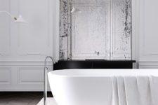 a minimalist Parisian bathroom with a tub on a stone platform, a vintage mirror, stucco walls and catchy minimal lamps