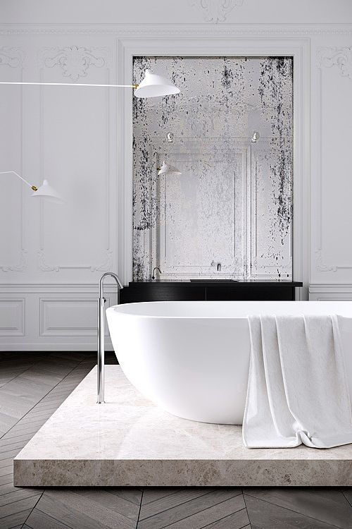 a minimalist Parisian bathroom with a tub on a stone platform, a vintage mirror, stucco walls and catchy minimal lamps