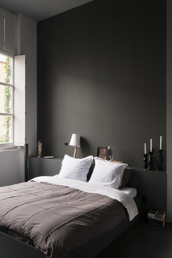 a minimalist bedroom with a black statement wall, a shelf, a built-in bed and white lamps