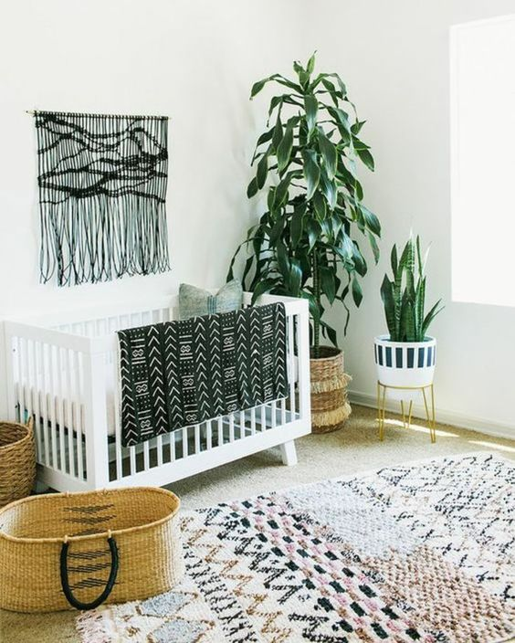 a monochromatic boho nursery with a black macrame hanging, a printed rug, a folksy print blanket and potted plants