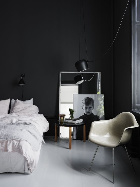 a moody Scandinavian bedroom with black walls, a white bed, a photo and a mirror plus a chair