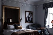 a moody refined bedroom with a statement chandelier, artworks, stucoo, a dark upholstered headboard and sophisticated furniture